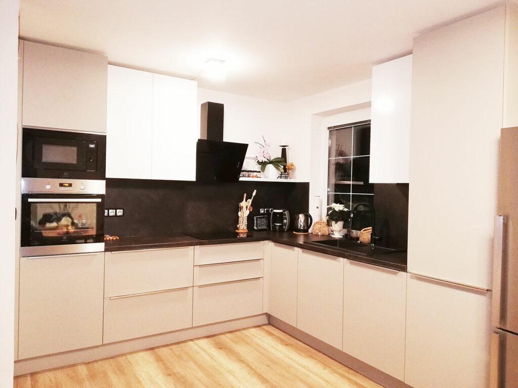 Kuchyň do L v krémové matné barvě a tmavu pracovní deskou.