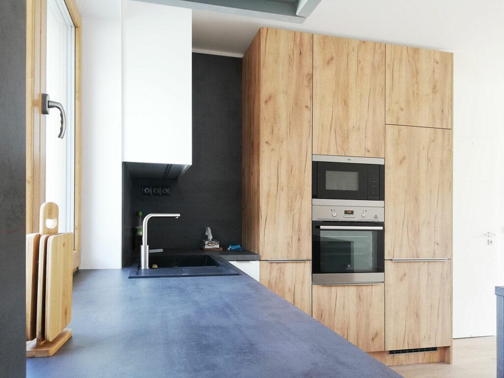 Kuchyň do L s ostrůvkem v kombinaci bílého lesku a dubu.