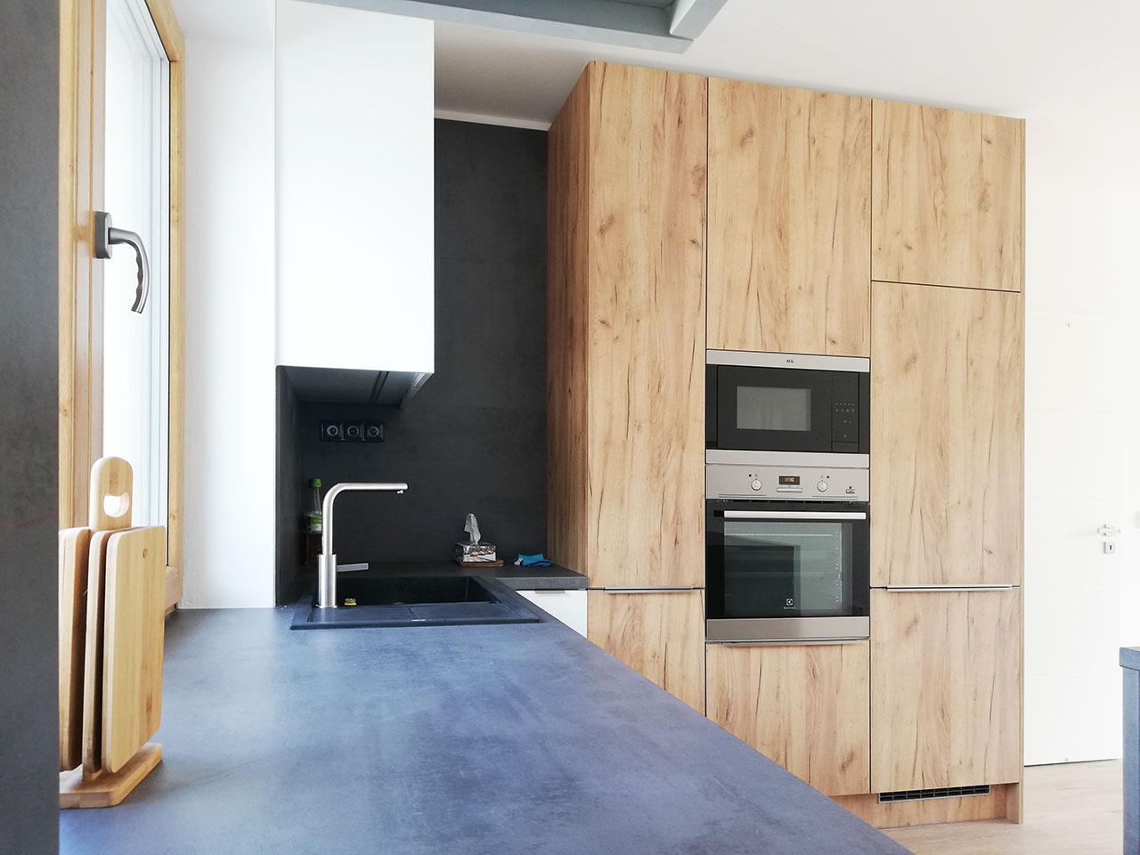 Realizace rohové kuchyně v rodinném domě v kombinaci bílé a dřevodekoru s tmavou pracovní deskou