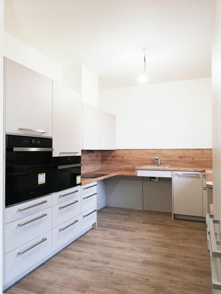 Kuchyň do U pro vozíčkáře v kombinaci bílé barvy a dubu.