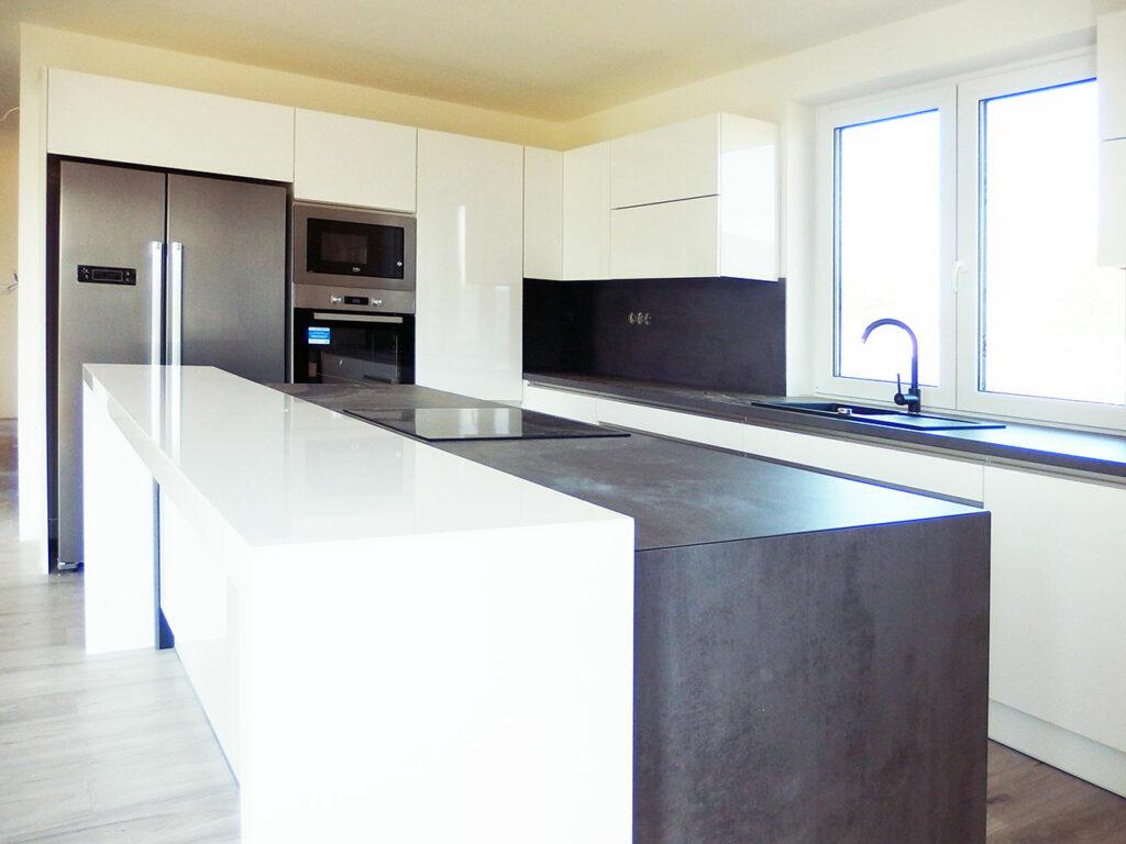 Kuchyň do L s ostrůvkem v bílé lesklé barvě a šedou pracovní deskou.