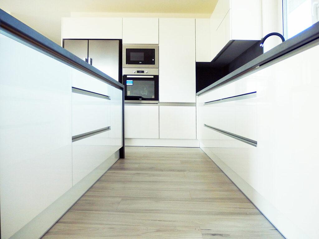Kuchyň do L s ostrůvkem v bílé lesklé barvě.