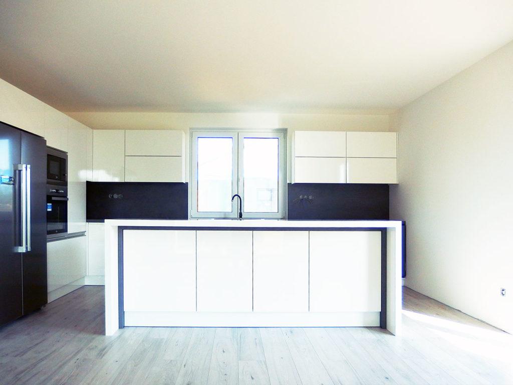 Realizace rohové kuchyně s ostrůvkem v bílém vysokém lesku a tmavou pracovní deskou do rodinného domu Praha 9