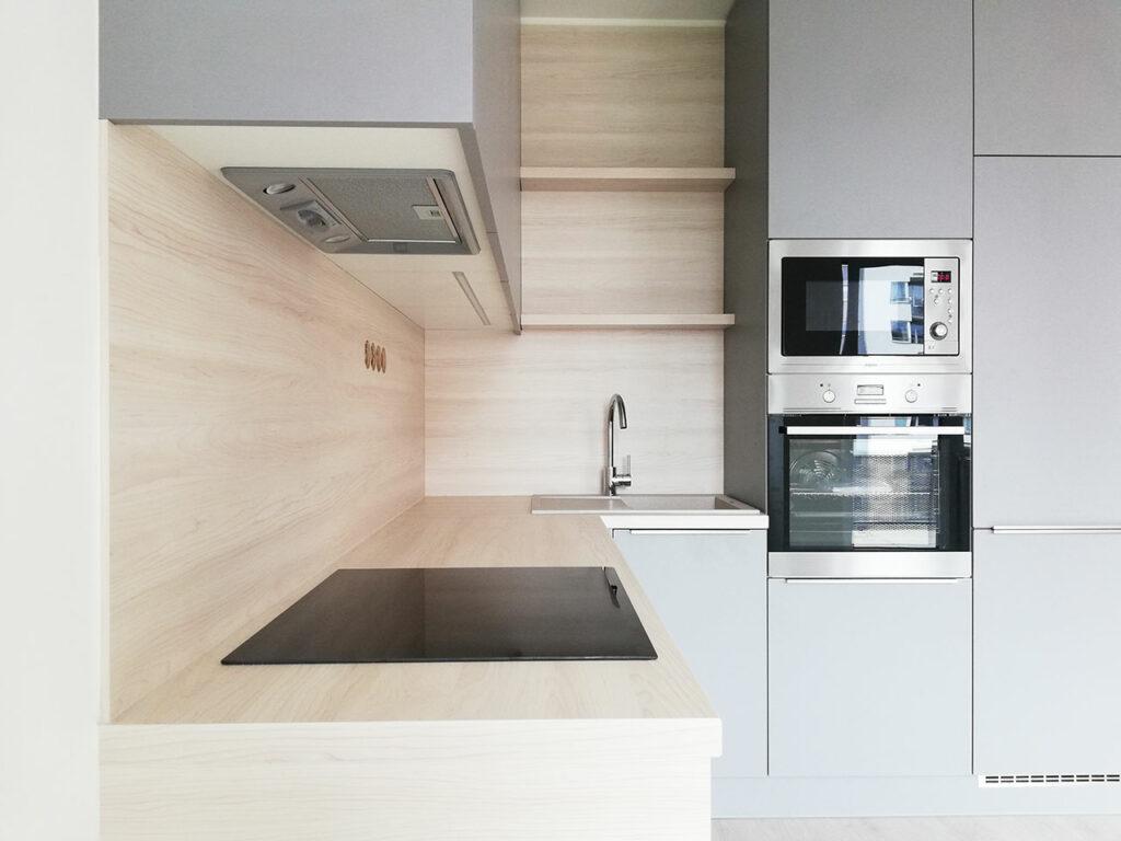 Kuchyň do L s dvířky v světlé šedé barvě a pracovní deskou ve světlém dřevě.