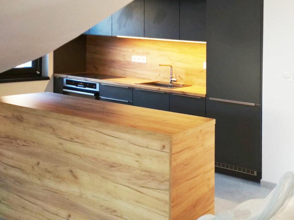 Rovná kuchyň s ostrůvkem v kombinaci tmavě šedé barvy a dubu.