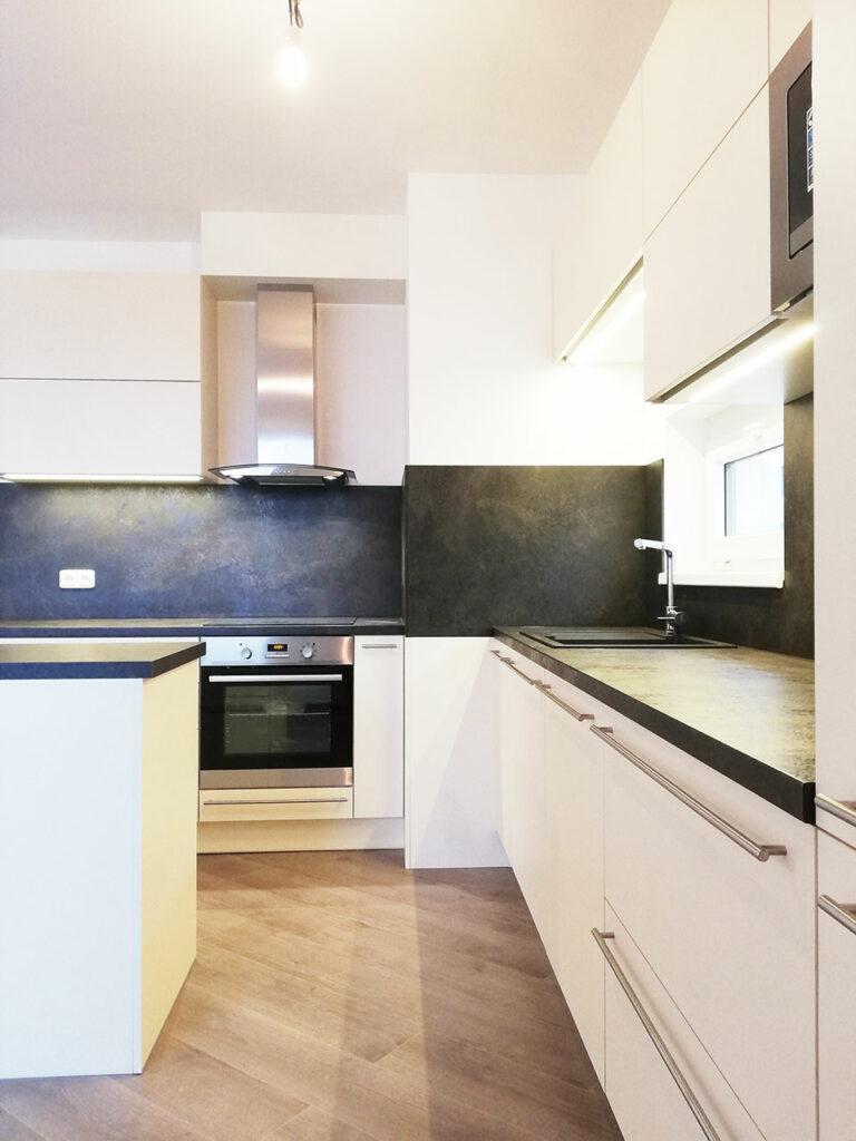Kuchyň do L s ostrůvkem ve stavělé barvě s tmavou pracovní deskou.