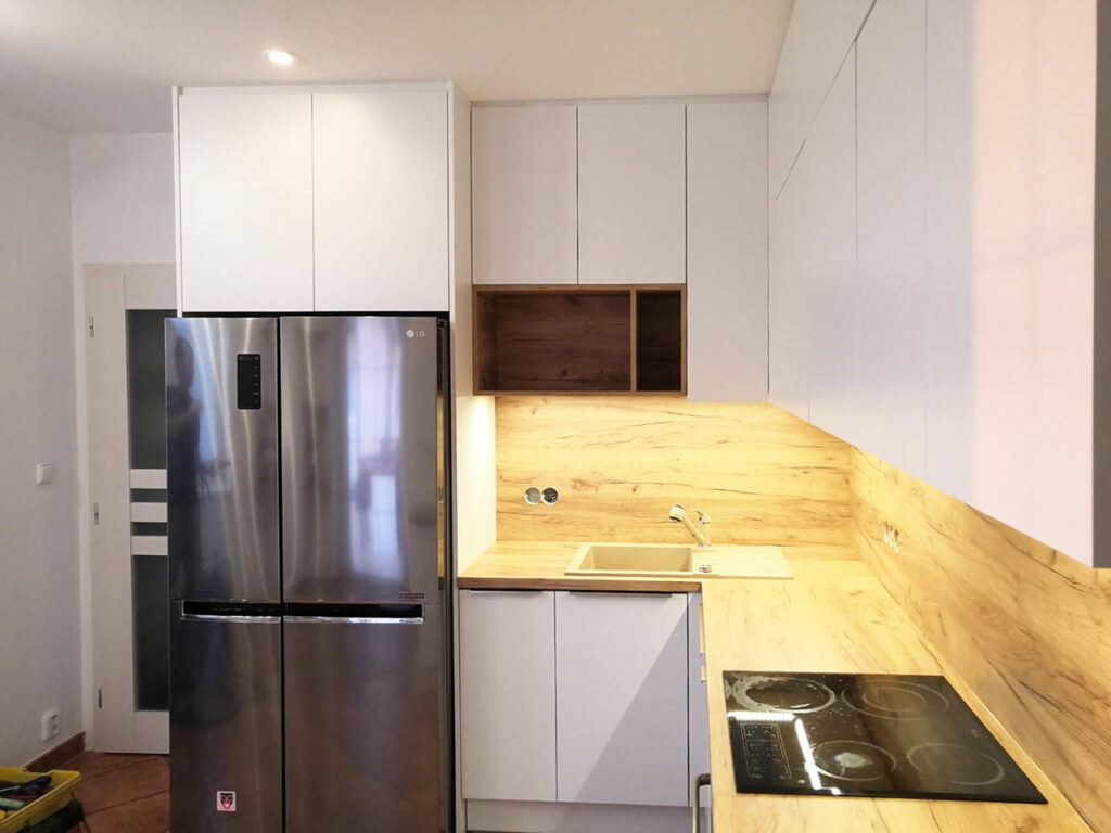 Kuchyň do U v kombinaci bílých dvířek a dřevěné pracovní desky a zástěny.