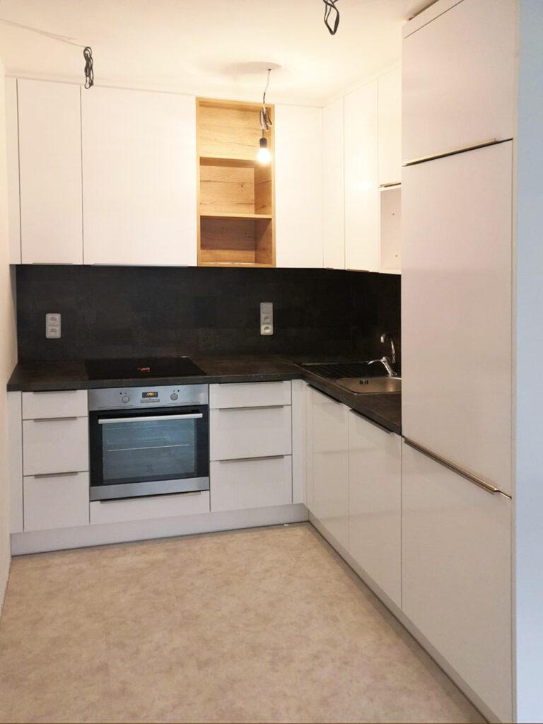 Kuchyň do L s býlým lesklými dvířky a otevřenou dřevěnou částí.