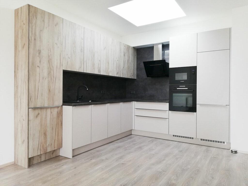 Kuchyň do L v kombinaci světle šedé barvy a světlého dubu.
