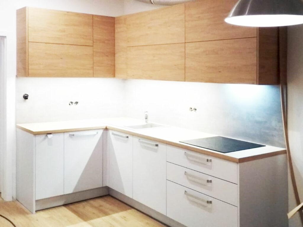 Kuchyň do L kombinaci bílé matné barvy na spodních skříňkách a dekoru dub na horních skříňkách.