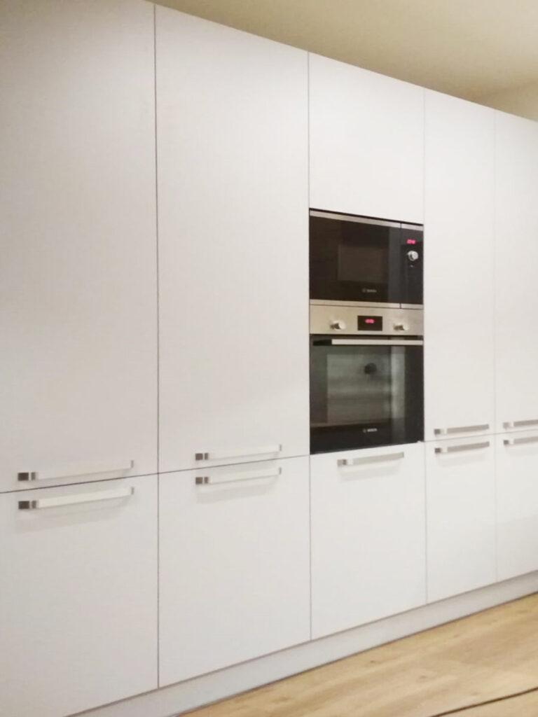 Rovná část kuchyně s vysokými skříňkami v bílé barvě.