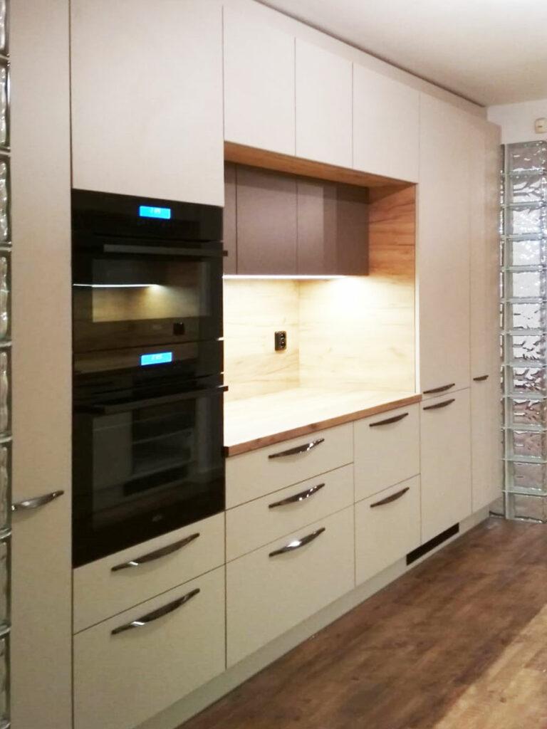 Rovná kuchyň v krémové barvě a dřevěnou pracovní deskou a zástěnou