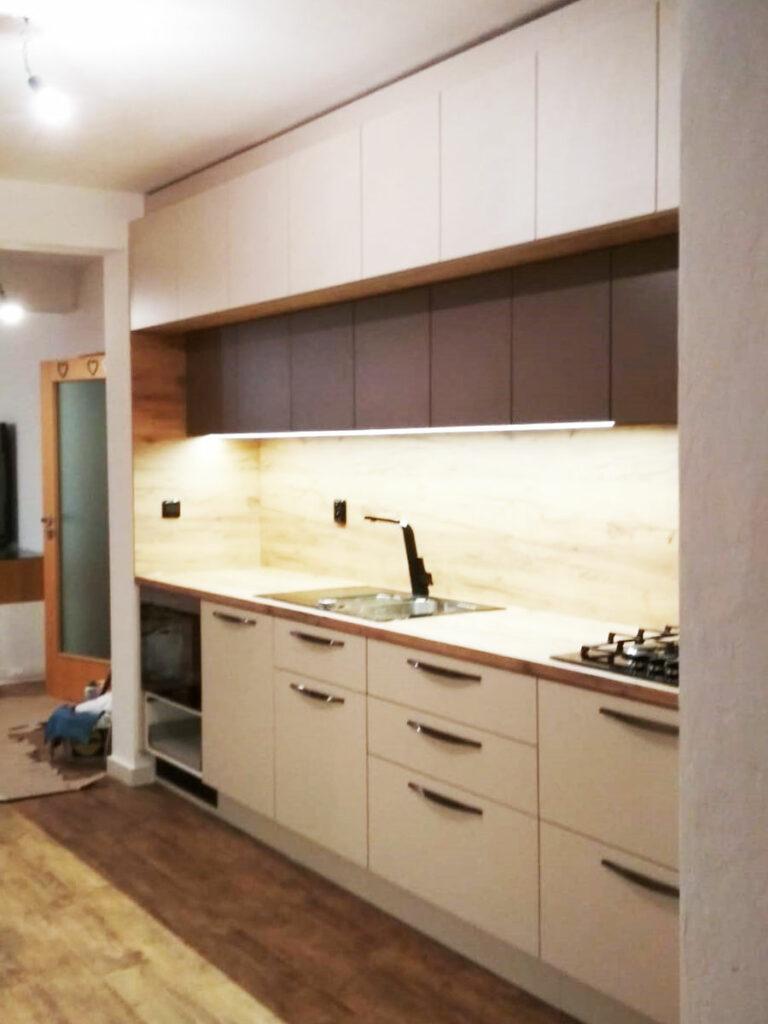 Rovná kuchyň v krémové barvě a dubovou pracovní deskou a zástěnou