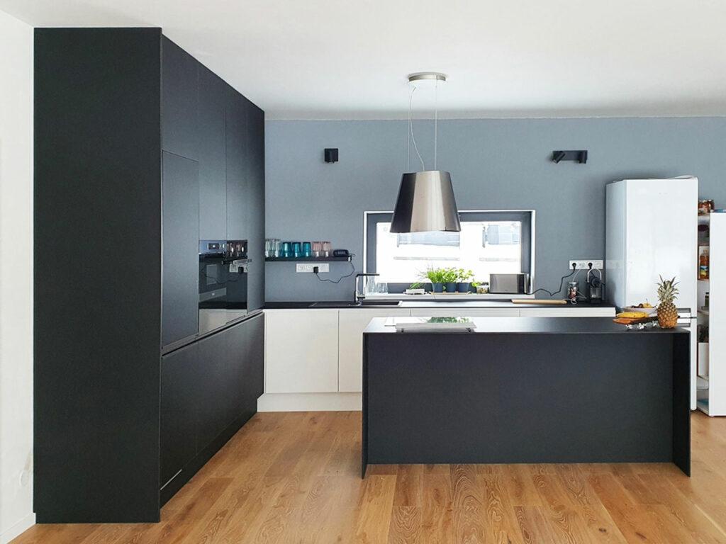 Krásná kuchyň v kombinaci bílého lesku a černého matu. Vše završeno tenkou pracovní deskou z kompaktního laminátu a úchytkami lakovanými v barvách kuchyně.