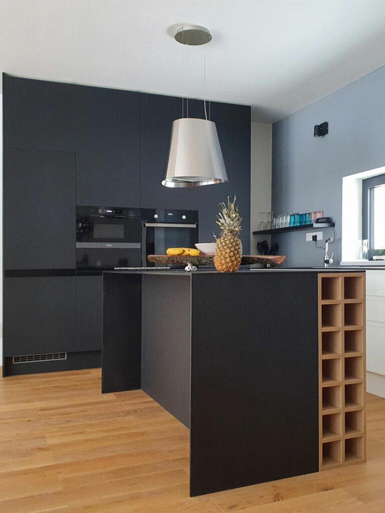 Krásná kuchyň s ostrůvkem v kombinaci bílého lesku a černého matu. Vše završeno tenkou pracovní deskou z kompaktního laminátu a úchytkami lakovanými v barvách kuchyně.