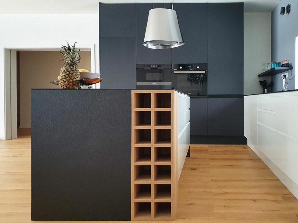 Kuchyň do L s ostrůvkem v kombinaci bílého lesku a černého matu. Vše završeno tenkou pracovní deskou z kompaktního laminátu a úchytkami lakovanými v barvách kuchyně.