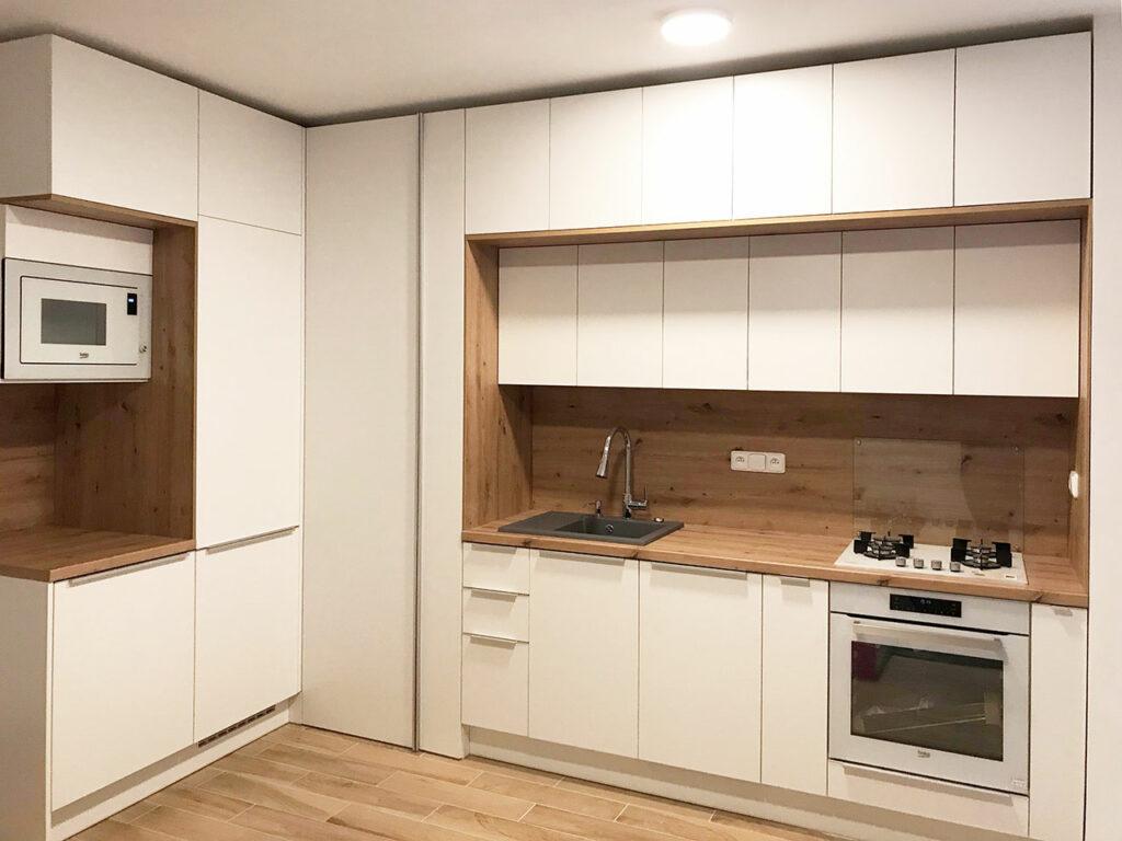 Kuchyň do L v oblíbené kombinaci bílé a přírodního dubového dřeva, která se hned tak nekouká.