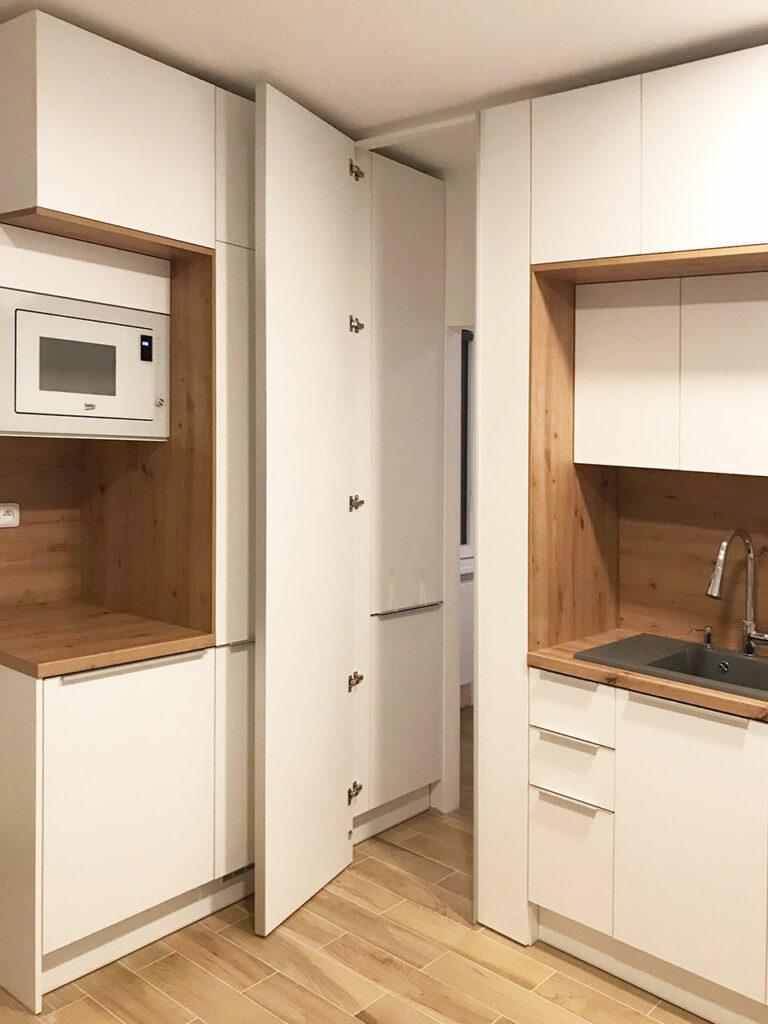 Kuchyň  do L v oblíbené kombinaci bílé a přírodního dubového dřeva. Část kuchyně funguje jako prostup do ložnice.