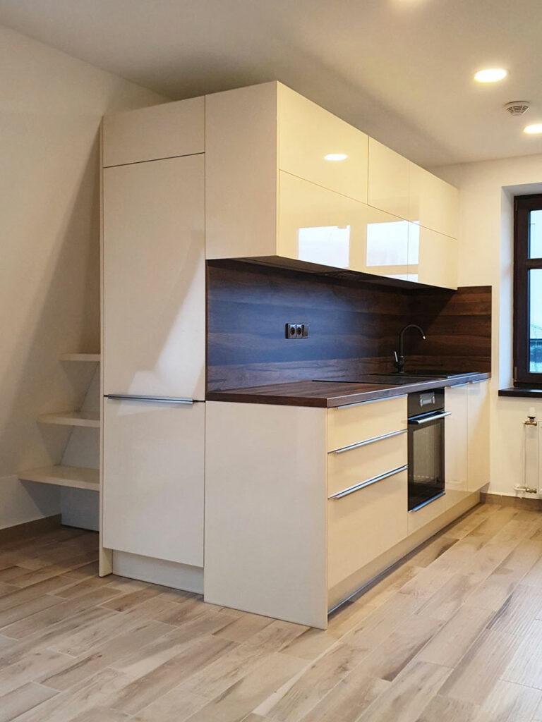 Kuchyň do atypyckého prostoru v podkroví v krémovém lesku.