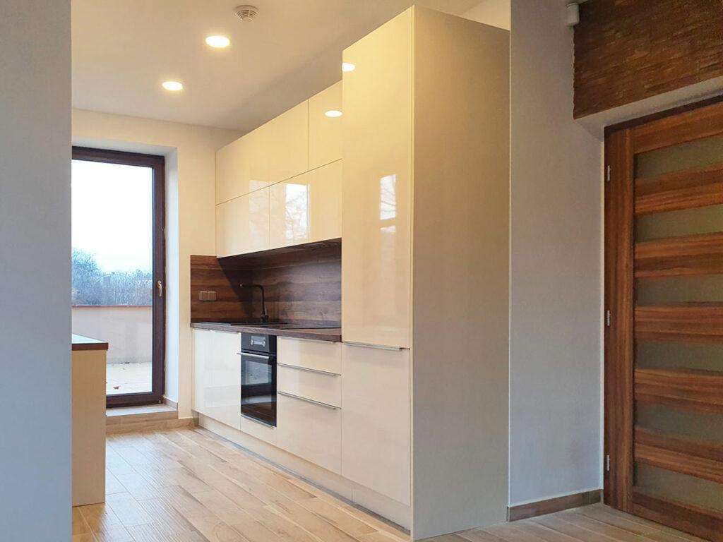 Rovná kuchyň v krémovém lesku s dřevěnou pracovní deskou a zástěnou.