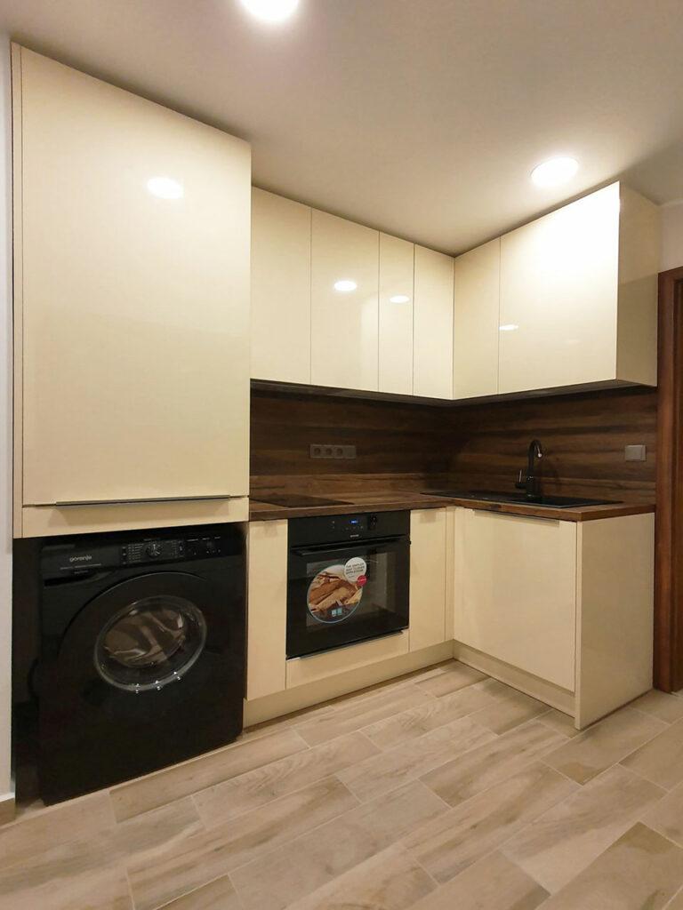Kuchyň do L v krémovém lesku s pracovní deskou a zástěnou v dekoru ořechu a zabudovanou pračkou.