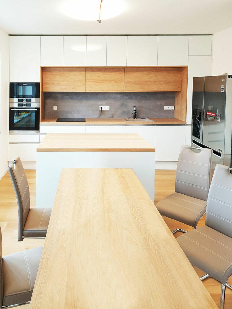 Rovná kuchyň s ostrůvkem jídelním stolem v kombinaci bílé lesklé a dubu.