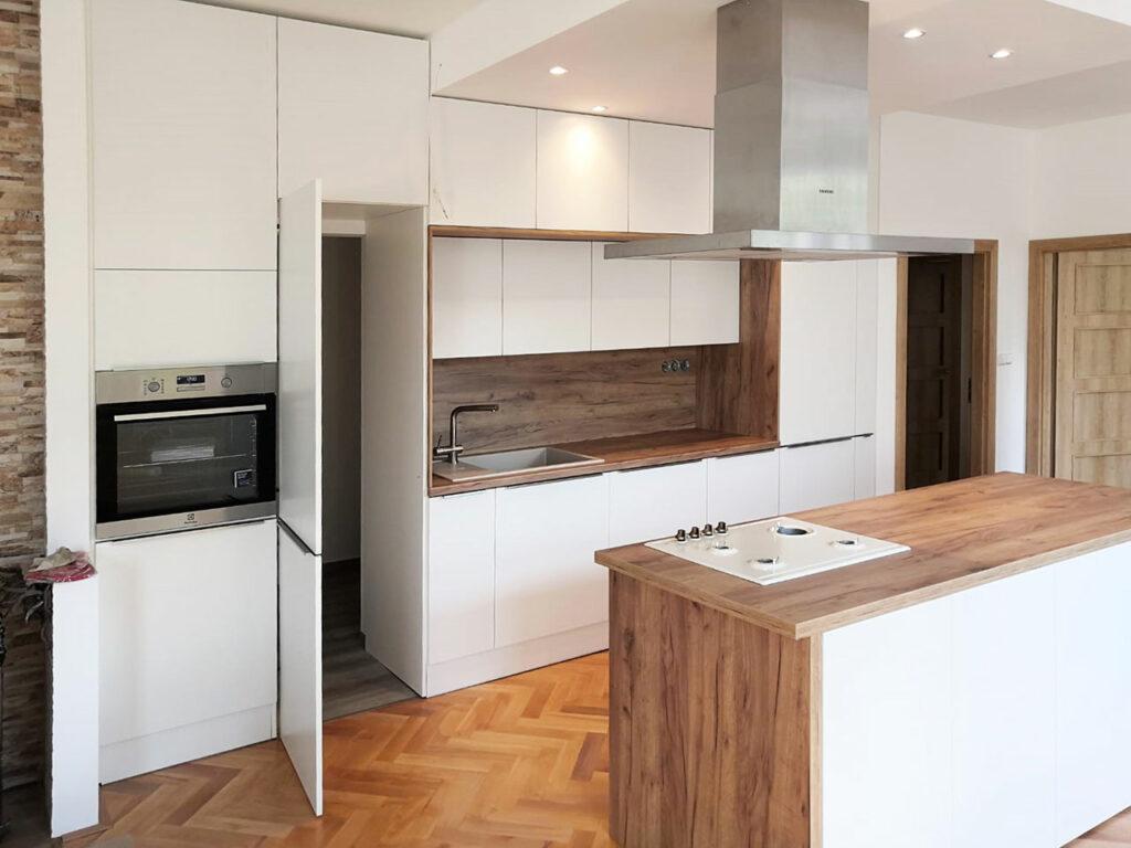 Rovná kcuhyň s ostrůvkem v bílé matné barvě a dubovou pracovní deskou a zástěnou. V kuchyni je skrytý průchod do špajzu.