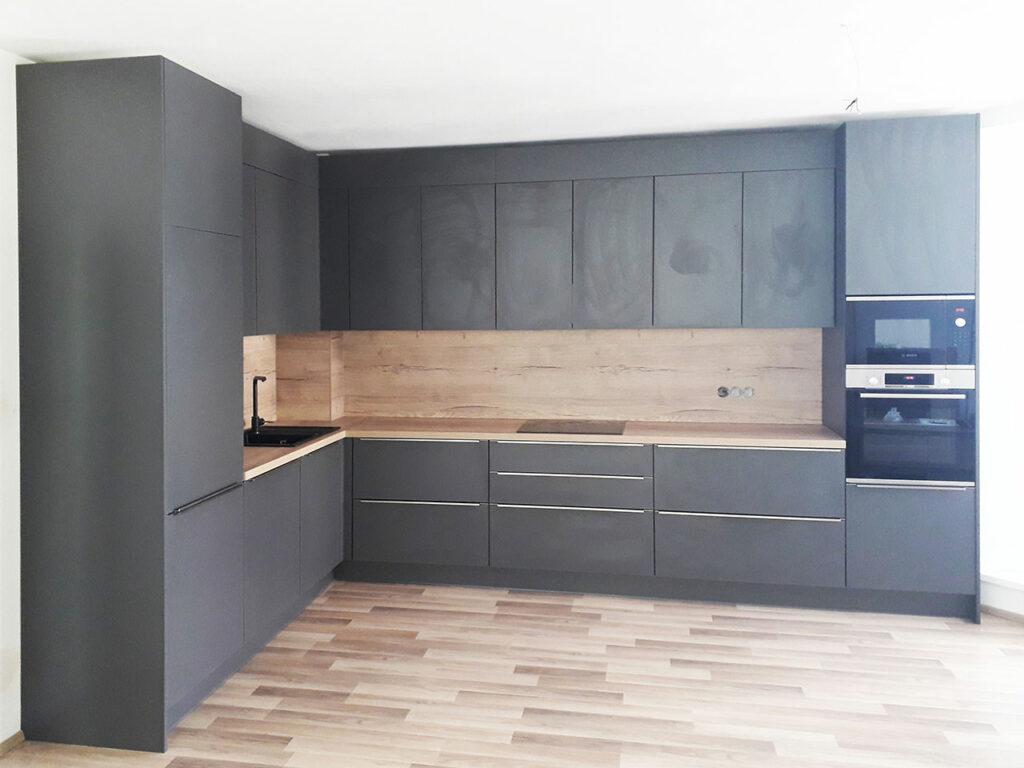 Kuchyň do L v šedé antracitové barvě a dubovou pracovní deskou a zástěnou.