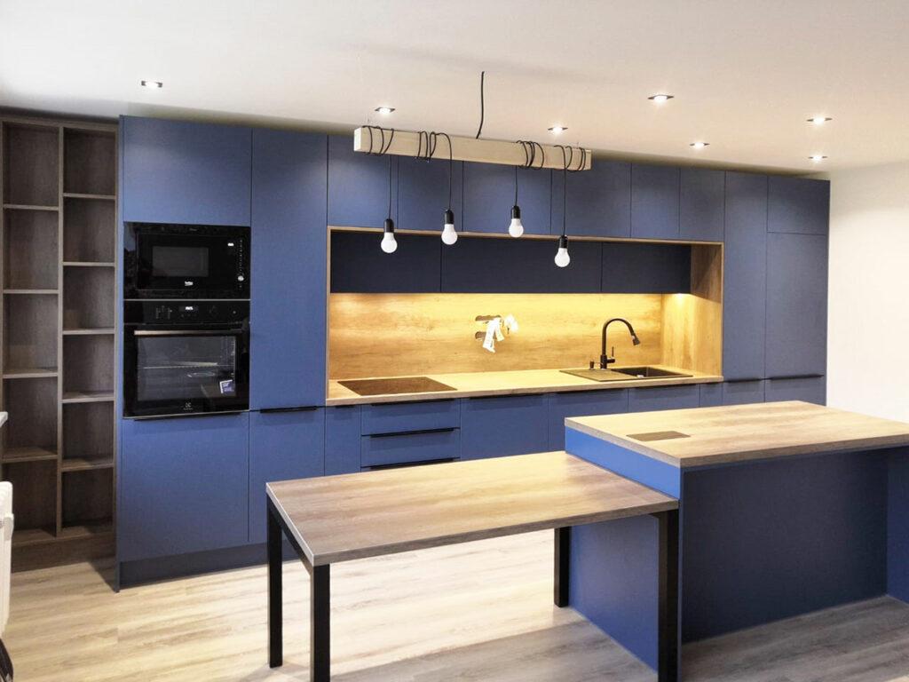 Rovná kuchyň v modré barvě s dřevěnou pracovní deskou a zástěnou.