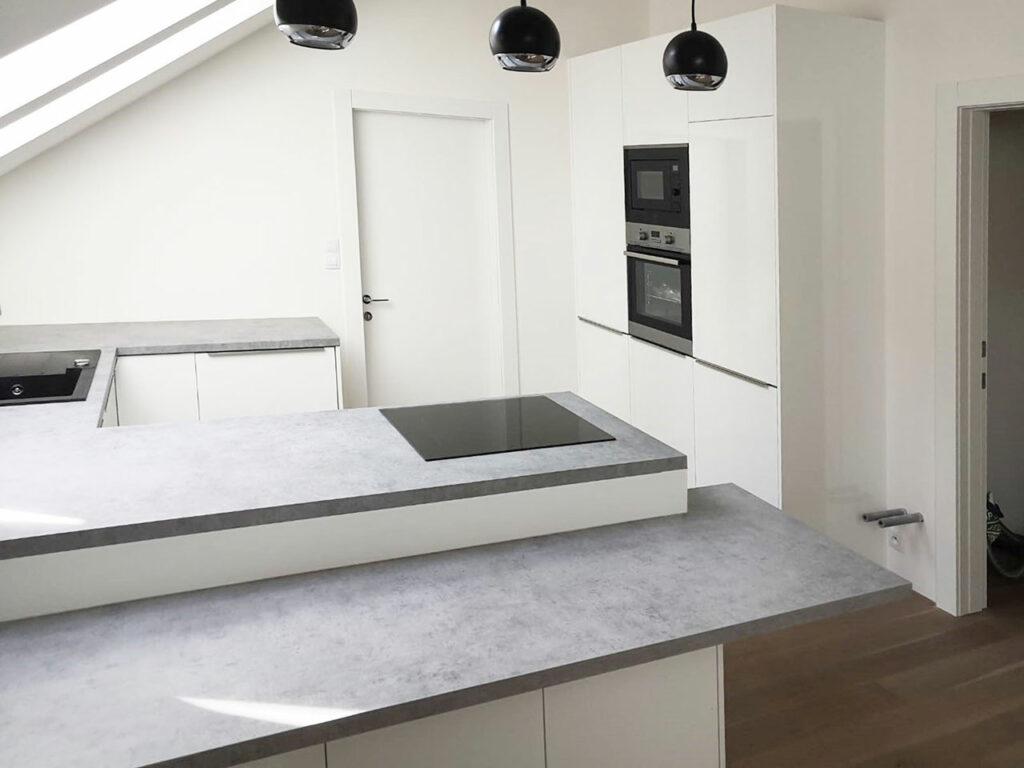 Kuchyň do U do podkroví v bílé barvě a betonovou pracovní deskou.