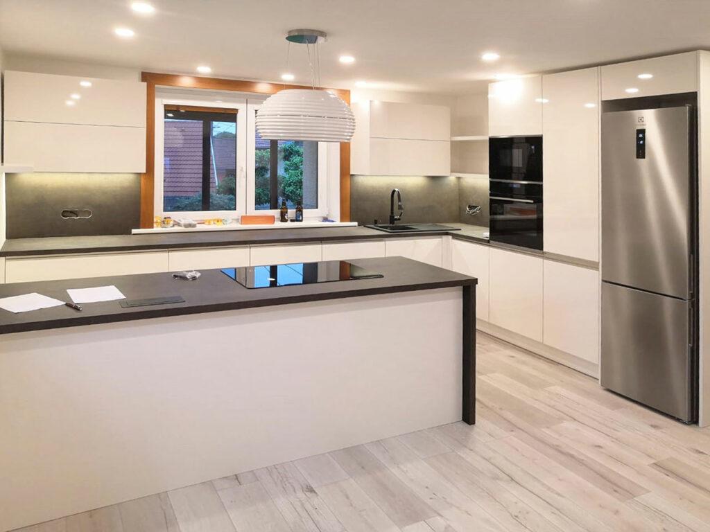 Kuchyň do L s ostrůvkem v bílé lesklé barvě a tmavou pracovní deskou.