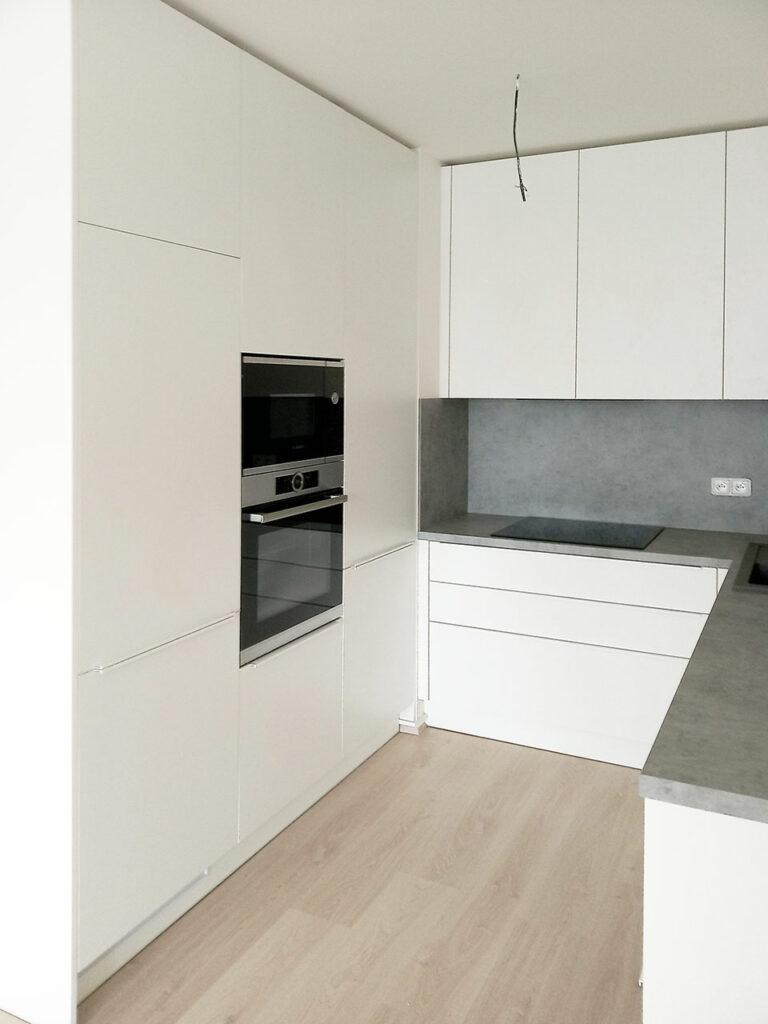 Bílá kuchyň do U s pracovní deskou a zástěnou v dekoru světlý beton.