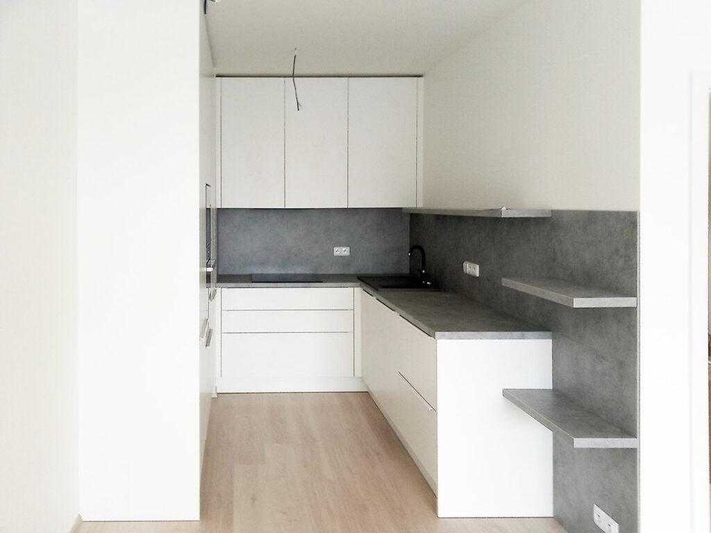 Bílá kuchyň do U s pracovní deskou, zástěnou a poličkami v dekoru světlý beton.