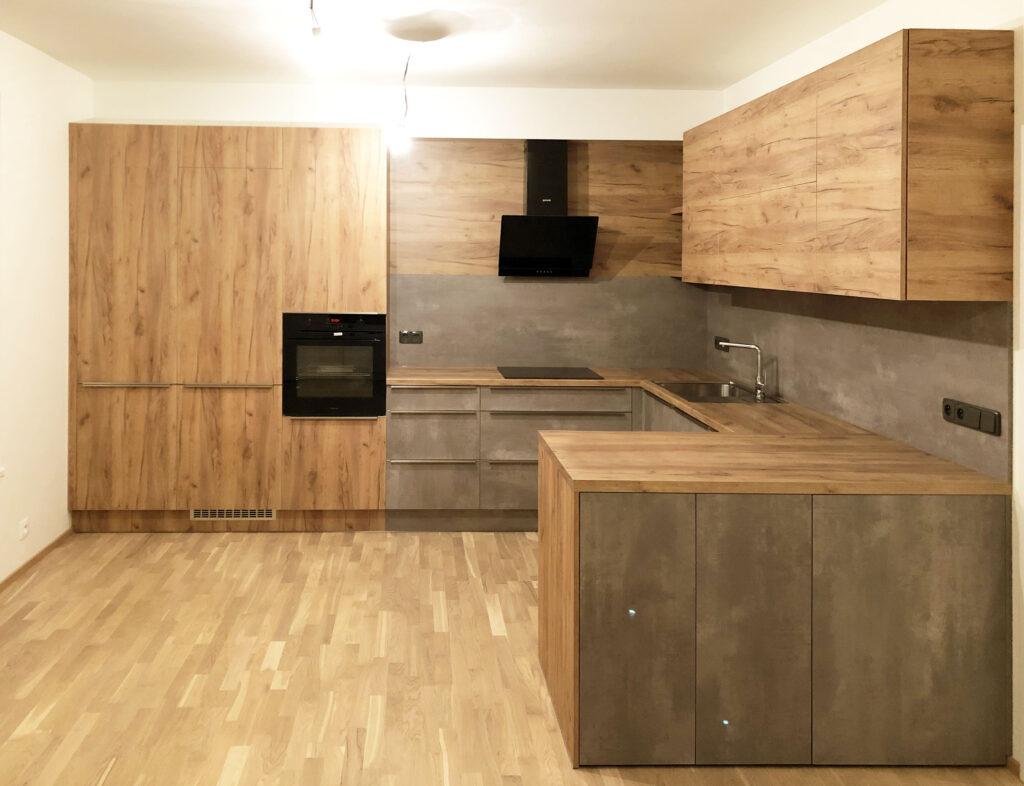 Velká kuchyň do U v kombinaci dub a betonová stěrka.