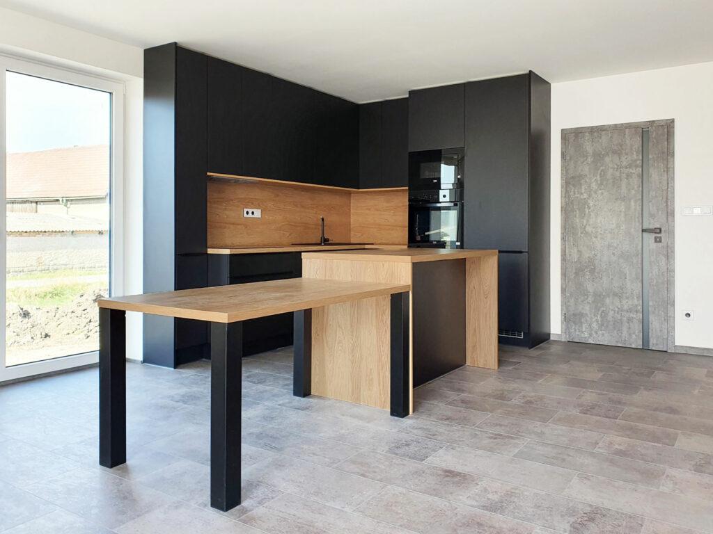 Kuchyň do L s ostrůvkem a jídelním stolem v kombinaci černé matné a přírodního dubu.